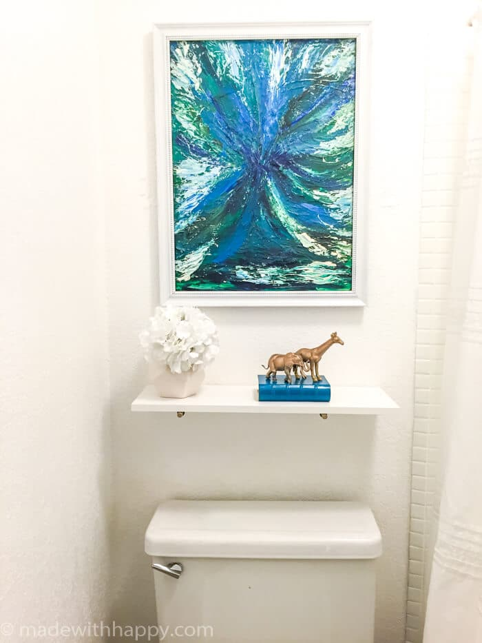 50 dollar bathroom makeover.  We turned this off-white and brown 80's bathroom into a modern dream with just a few changes.  We were able to paint the tile and paint the vanity top changing the look of the bathroom dramatically.  Bathroom Makeover on a budget.  DIY Bathroom.  Modern Blue Bathroom.  www.madewithhappy.com