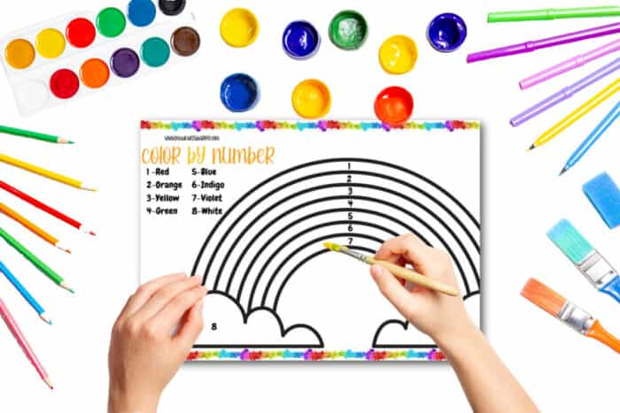 child painting a color by numbers rainbow sheet