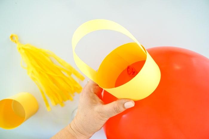 taping paper lantern topper to balloon