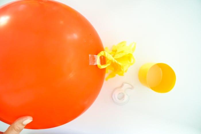 tape piece attaching tassel to bottom of balloon