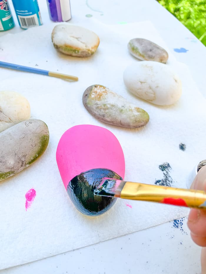 painting the head of a ladybug on a rock