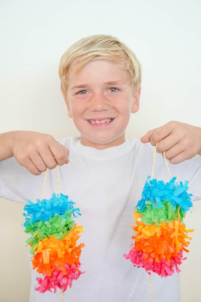 boy holding two mini rainbow pinatas