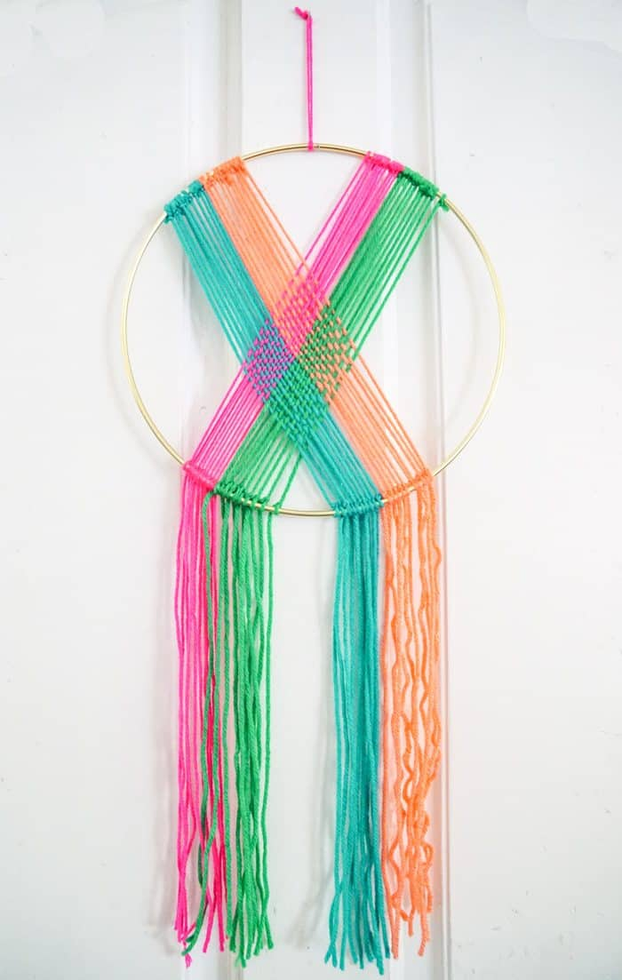 Colorful Wall Hanging with yarn.Modern Christmas Wreath.  Colorful Wall Hang.  Simple modern Christmas decor. DIY Wall Hang Ideas. Modern Wall Hangs with a lot of color. Colorful Wall Hangs. Christmas wreaths made out of yarn.