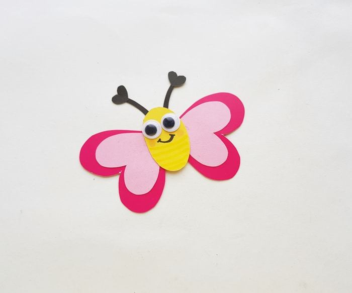 add googly eyes and smile to butterfly