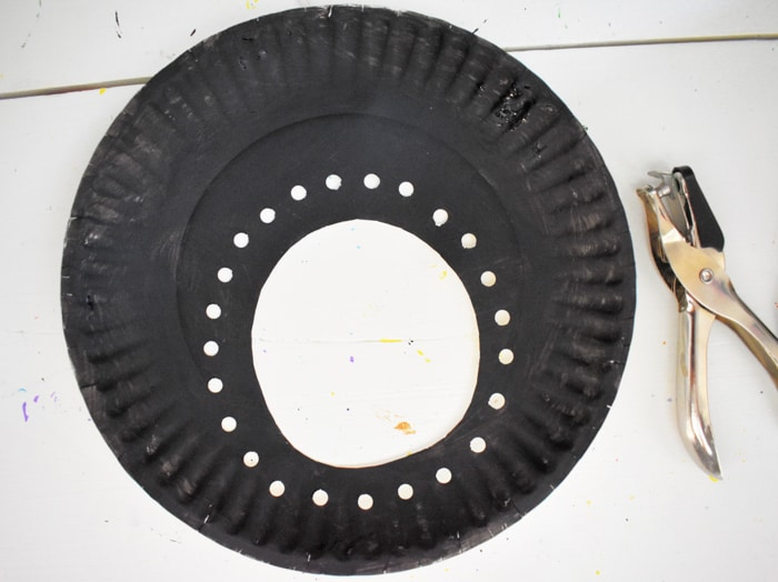 hole punch around cut out circle on paper plate