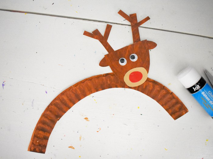 Gluing the head on the reindeer craft