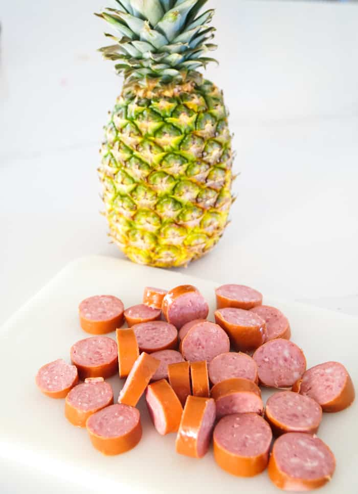 cut up sausage in front of a pineapple