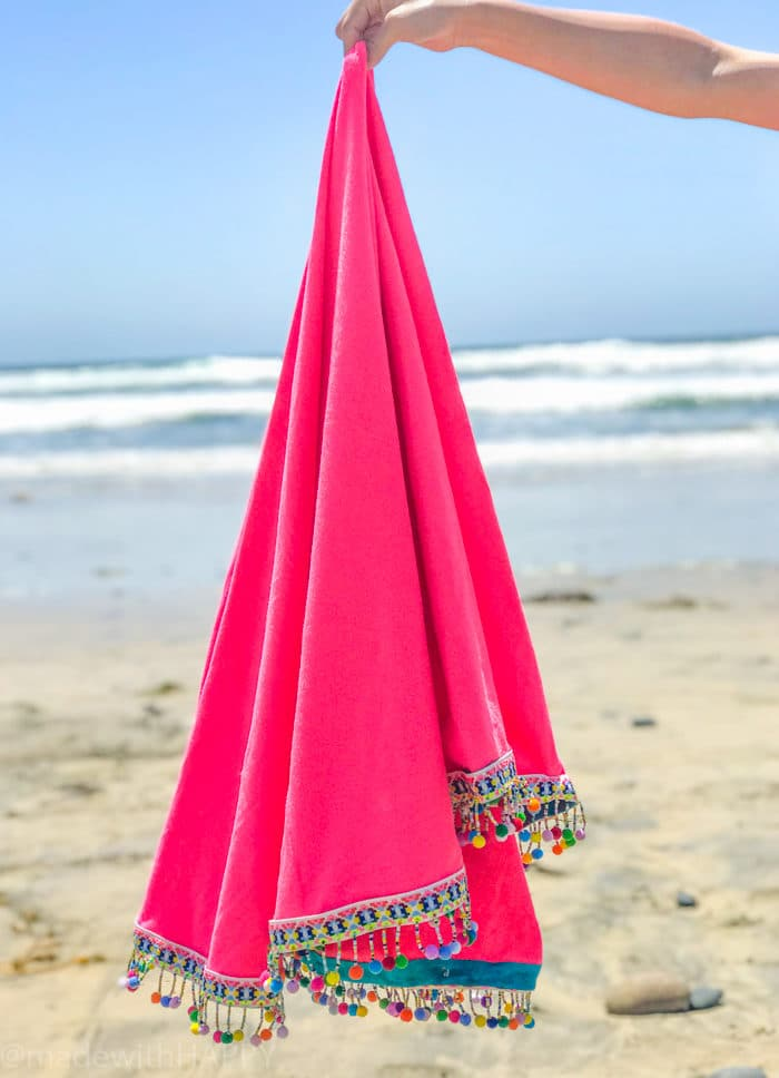 hand holding pink blanket at beach