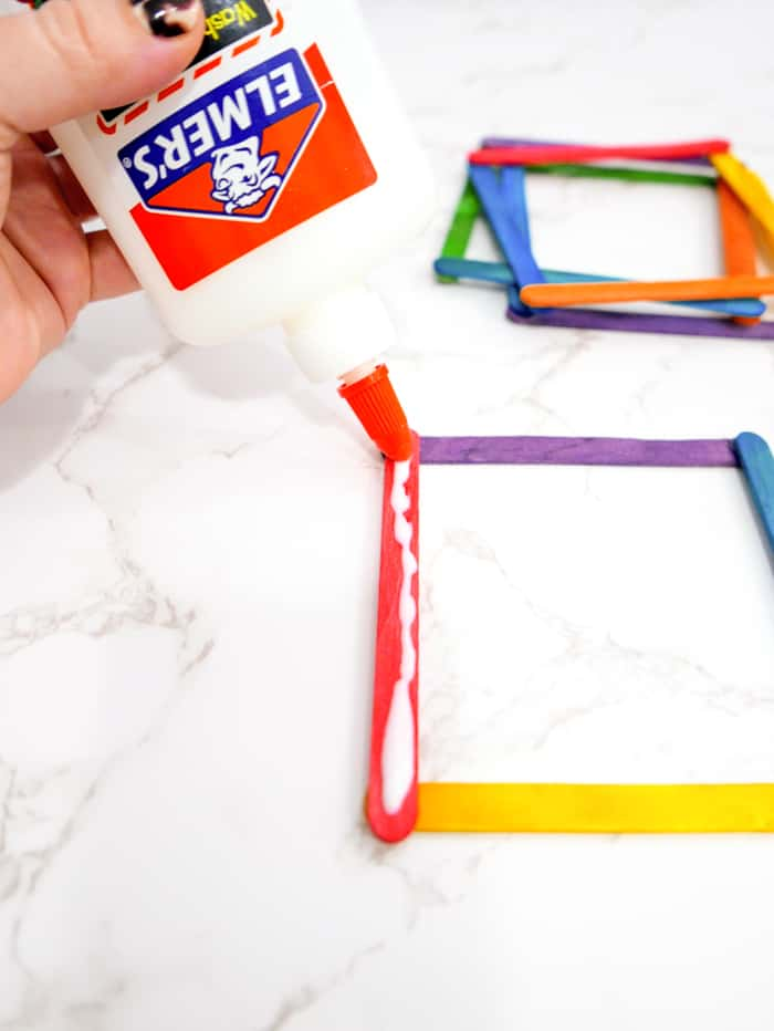 Place glue along each of the sticks on one side.