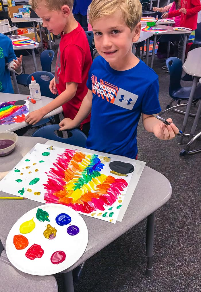 1st Grader painting rainbow. St. Patrick's Day Rainbow Art Project. Looking for St. Patricks Day Rainbow Art for 1st Graders, then we have the perfect project.