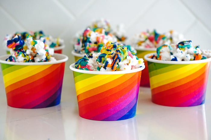 Rainbow popcorn in rainbow bowls. There is nothing sweeter than turning up the color on your popcorn snack with this super fun rainbow popcorn. Rainbow snacks for St. Patrick's Day. Rainbow food.