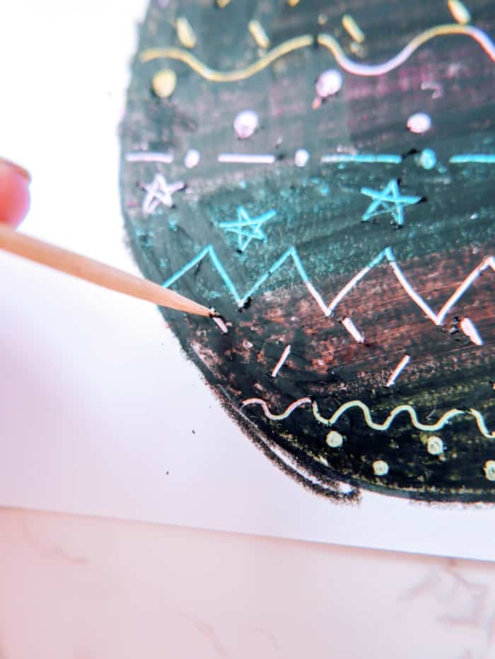 3. Using a wooden skewer or mechanical pencil with the lead removed, begin etching designs into the black crayon. You can draw lines, stars, circles or any shape. Just have fun, and make the design all your own.