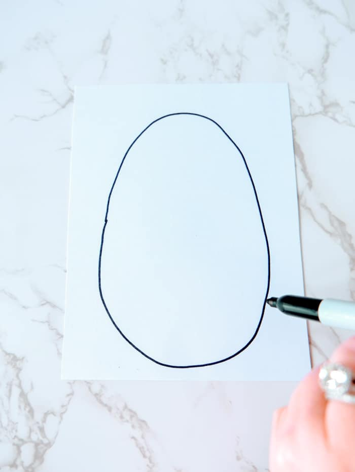 1. Draw a large oval egg shape on the white cardstock with a sharpie marker. Color the inside of the egg in straight or diagonal lines in varying colors. Make sure to color the entire inside of the egg very well, and not leave any part of it uncolored.