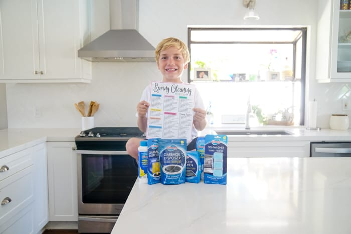 Child on Counter with Cleaning Supplies and Spring Checklist
