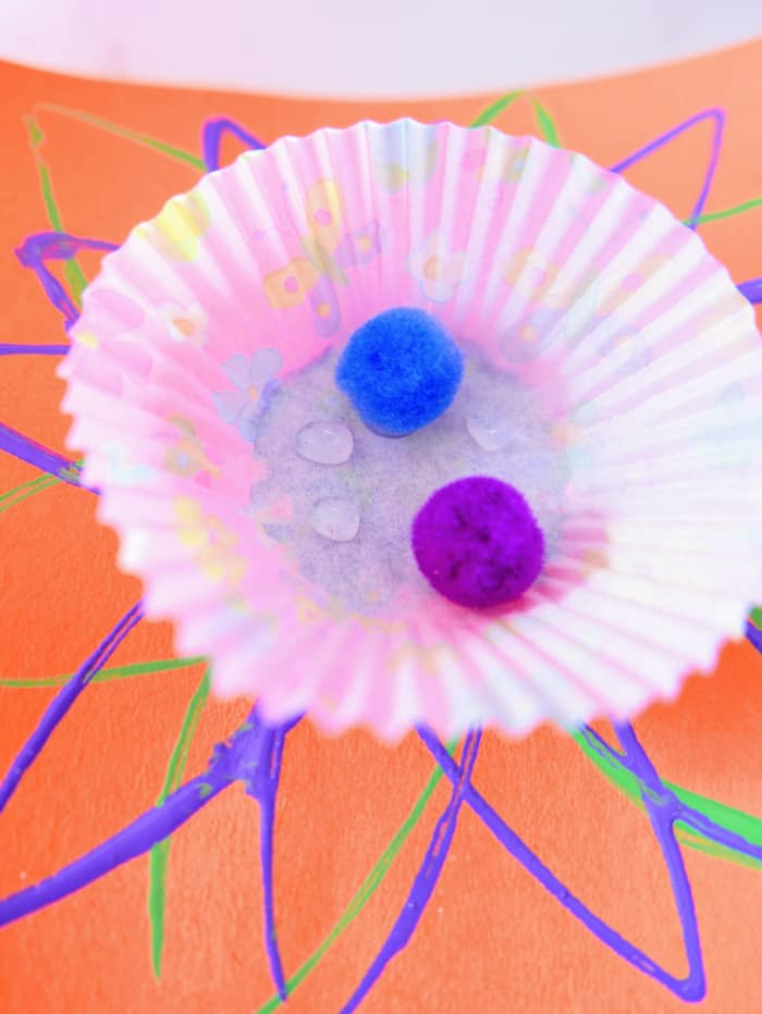 glue pom poms to middle of cupcake liner