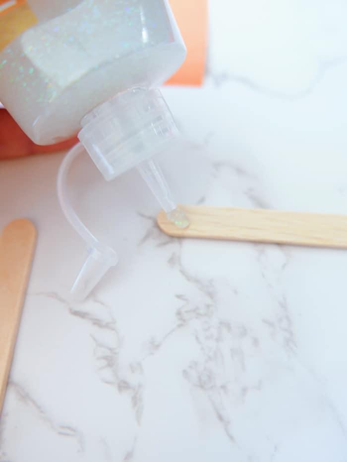 adding glue to popsicle stick