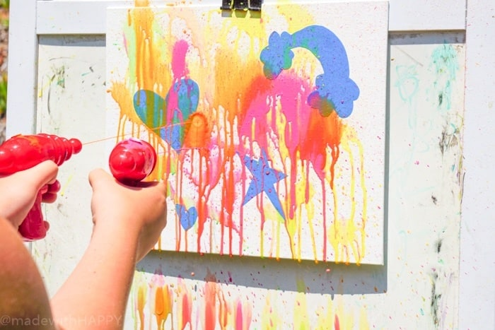 Fun Summer painting with water guns. Water gun painting. Looking for Summer activities for the kids? The kids LOVE water gun painting throughout the Summer.