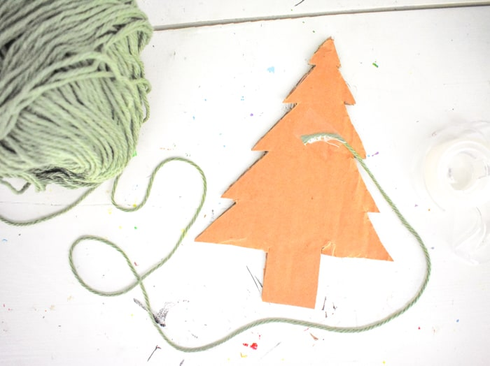 Now, cut a long strand of yarn. Tape one end to the back of the tree.