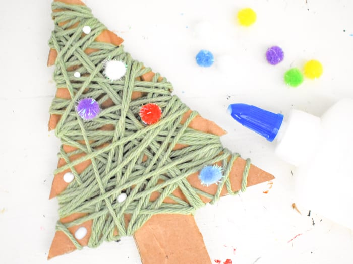 Then, use dots of glue to adorn the tree with your choice of decorations. We chose poms and sequins. You could also try gems, buttons, etc.